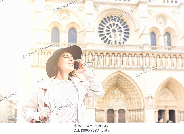 Stylish young woman talking on smartphone at Notre Dame, Paris, France