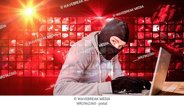 Digital composite image of hacker using laptop