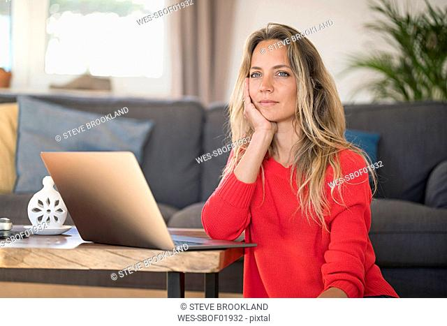 Pensive woman with laptop on coffee table at home