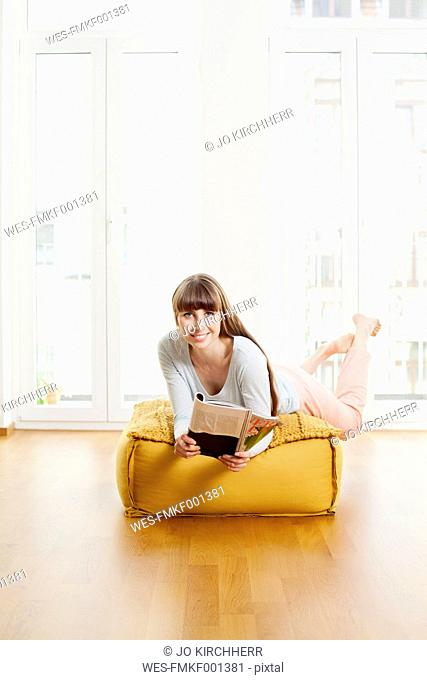 Relaxed woman reading magazine on ottoman at home