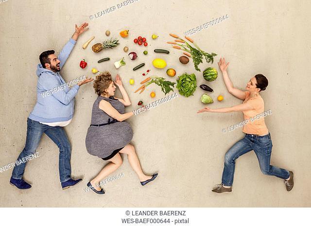 Men and woman with food against beige background