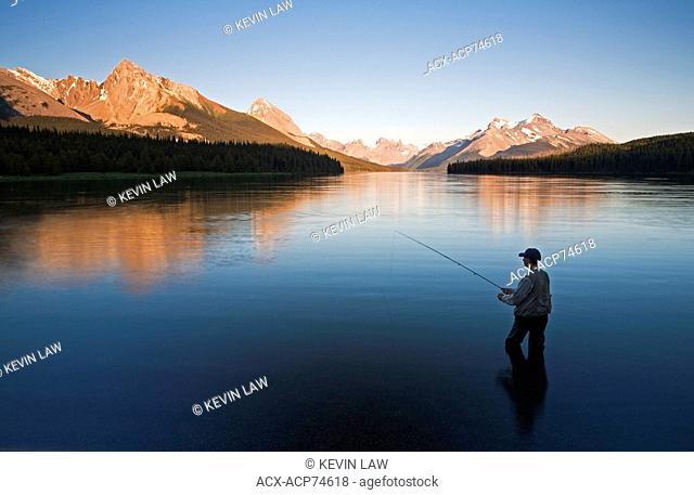 Middle age male fly fishing on Maligne Lake, Jasper National Park, Alberta, Canada