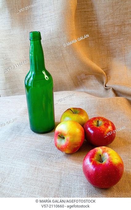 Asturian still life: bottle of cider and four apples. Asturias, Spain