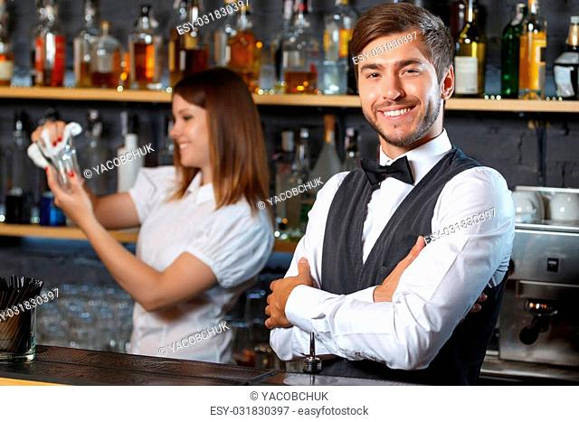 Portrait of a handsome bartender standing at the counter smiling and looking at the camera while a pretty waitress holding a glass and wiping it