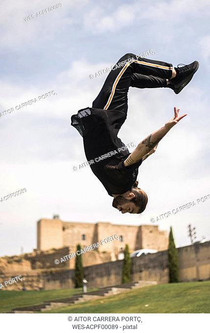 Spain, Lleida, tattooed man doing parkour in a park