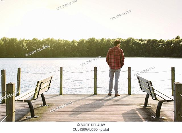 Young man standing on jetty looking across water