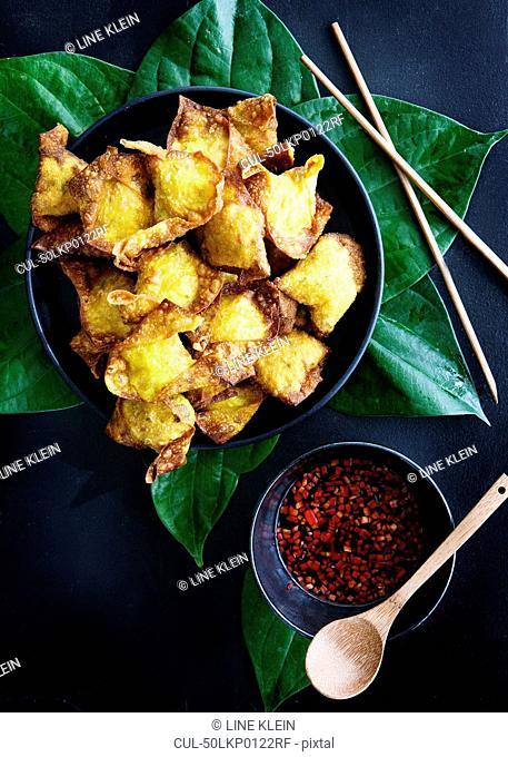 Plate of deep fried dumplings with sauce