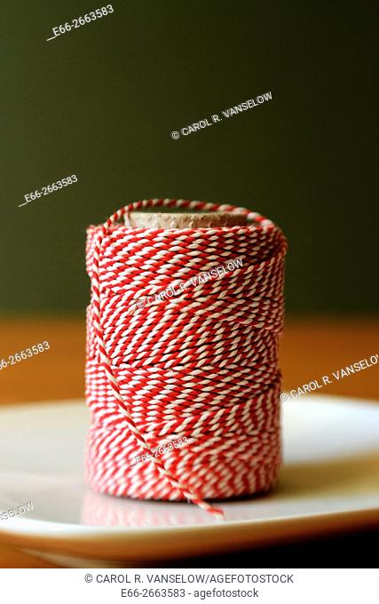 red and white string used in cooking. Sitting on white plate with dark green background. Shot with LensBaby for selective focus