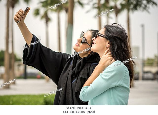 Young middle eastern woman wearing traditional clothing taking smartphone selfie with female friend, Dubai, United Arab Emirates