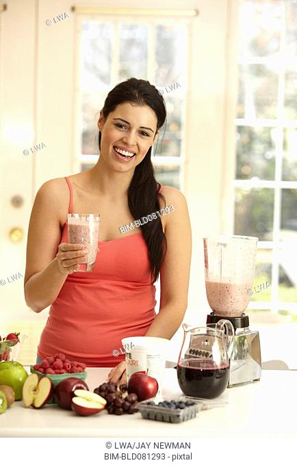 Hispanic woman making fruit smoothie