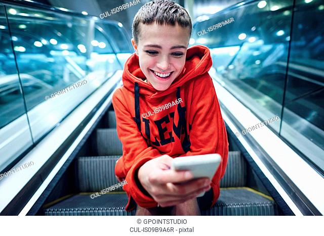 Short haired young woman moving down underground station escalator looking at smartphone
