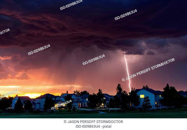 Forked lightning in orange sky over urban area, Aurora, Colorado, United States, North America