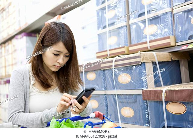 Young woman calculating prices in supermarket