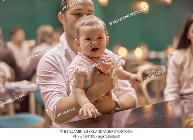 father with baby at table in restaurant, Vegan Oriental, Kismet, in Munich, Germany