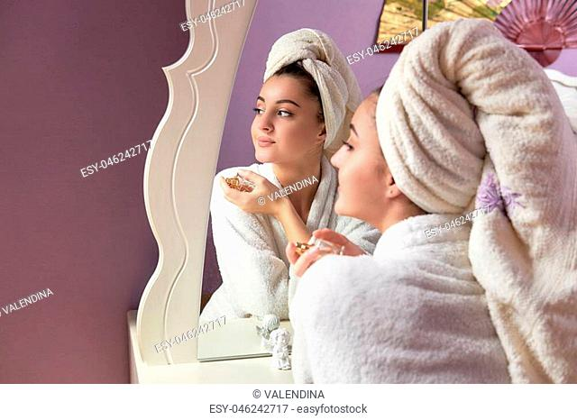 Portrait of beautiful girl in bathrobe and with towel on her head. Face of young beautiful healthy woman and reflection in the mirror, holds a bottle of perfume