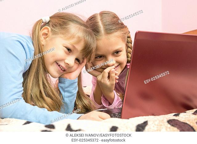 Sisters watching a cartoon on a laptop and laughing at a funny moment