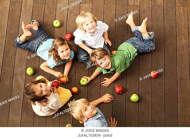 A group of young children seated on wooden decking surrounded by a selection of apples
