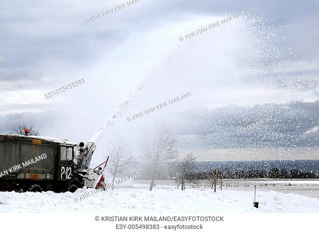 Highspraying snowblower at work. Scandinavia
