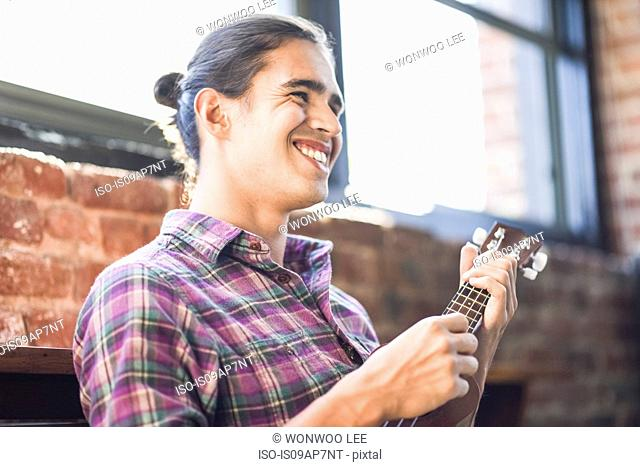 Young man playing ukulele