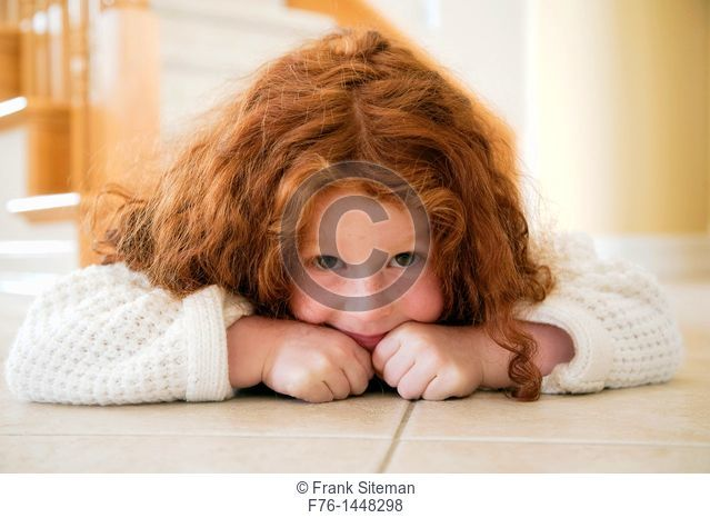 Portrait of five year old girl with red hair lying on tiles on floor