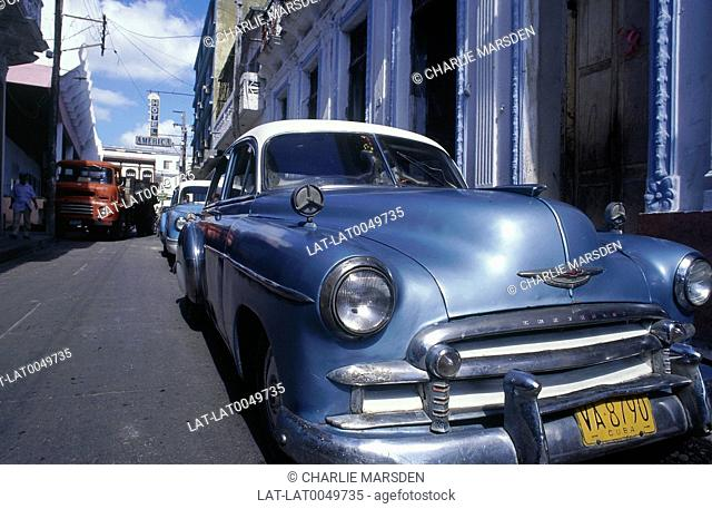 Two blue 1950s Chevrolet cars parked. Street scene. Hotels/ buildings