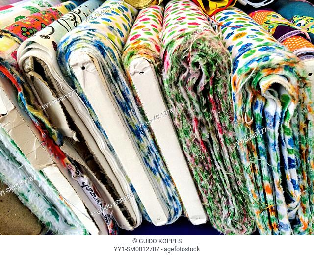 Tilburg, Netherlands. Rolls of colorful cloth stacked in a market stall for needlewomen to buy and use
