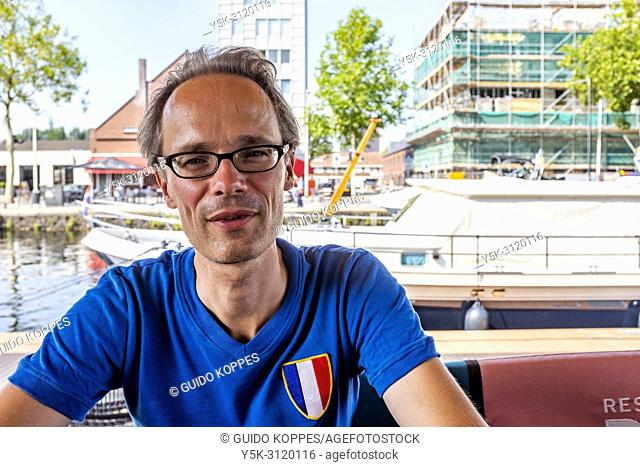 Tilburg, Netherlands. Portrait of a man, enjoying his free time at a terrace at City Harbour Piushaven