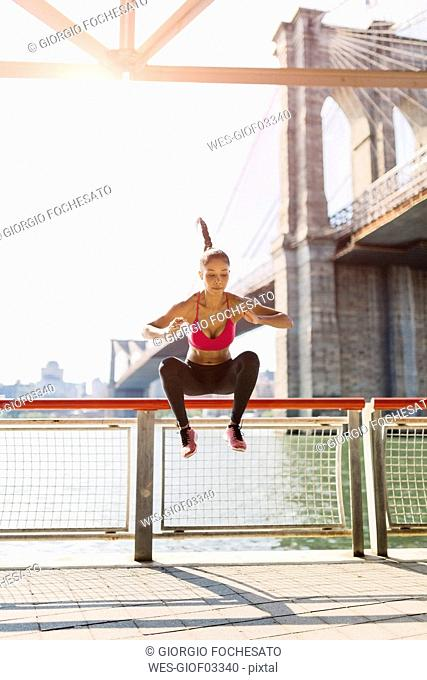 Female athlete training in Manhattan near Brooklyn Bridge, jumping mid air