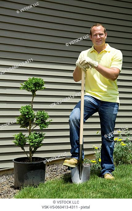 Man with shovel standing in front of house
