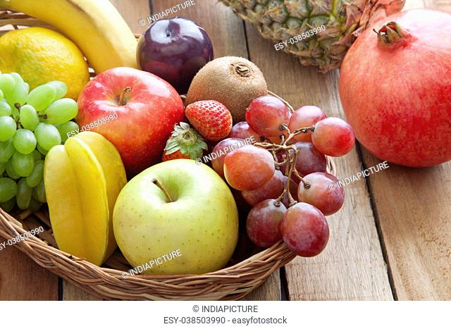 Wicker basket filled with fresh fruits against wooden background
