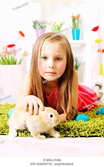 girl lying on the carpet with a rabbit