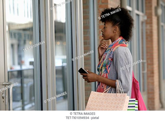Young woman looking at store window