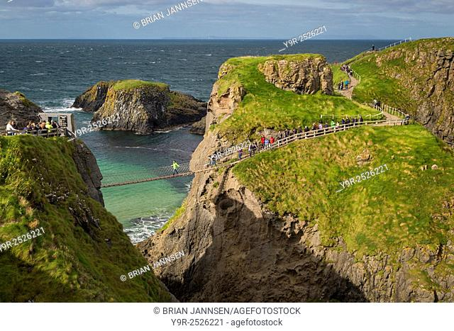 Tourists walk across the Carrick-a-Rede Rope Bridge along the north coast, County Antrim, Northern Ireland, UK
