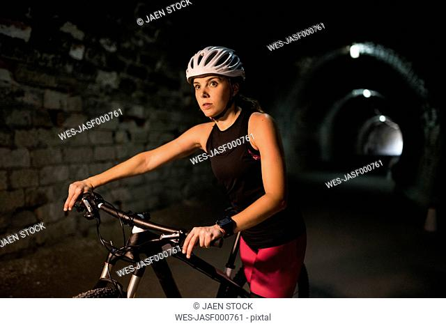 Sportive woman with bicycle in a tunnel