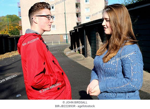 Teenagers chatting near flats