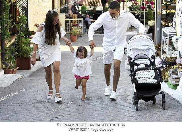 parents walking with toddler daughter in hands and buggy on street. In Chersonissos, Crete, Greece