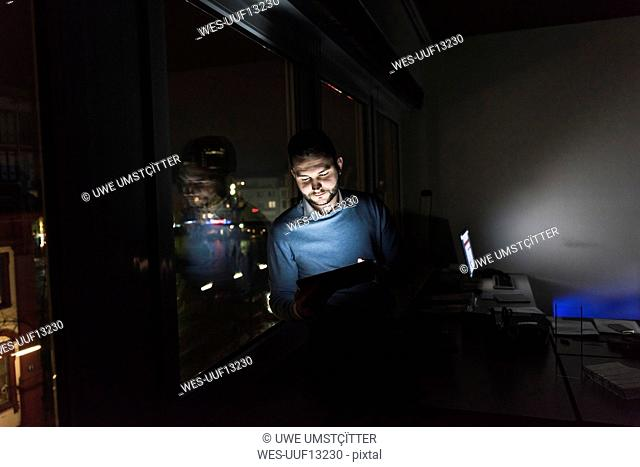 Businessman sitting on window sill in office at night using tablet