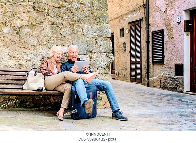 Tourist couple sitting on bench looking at digital tablet in Siena, Tuscany, Italy