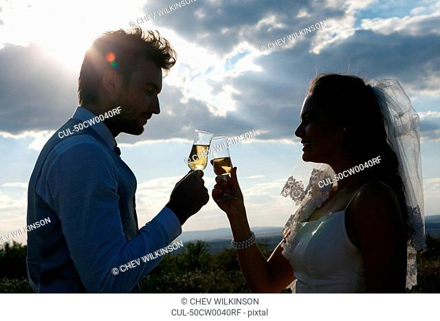 Newlywed couple having champagne