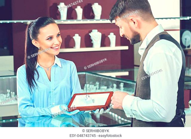 Friendly assistance. Beautiful young female jeweler smiling cheerfully showing a diamond ring to her male customer at the store wedding bridal jewelry buying...