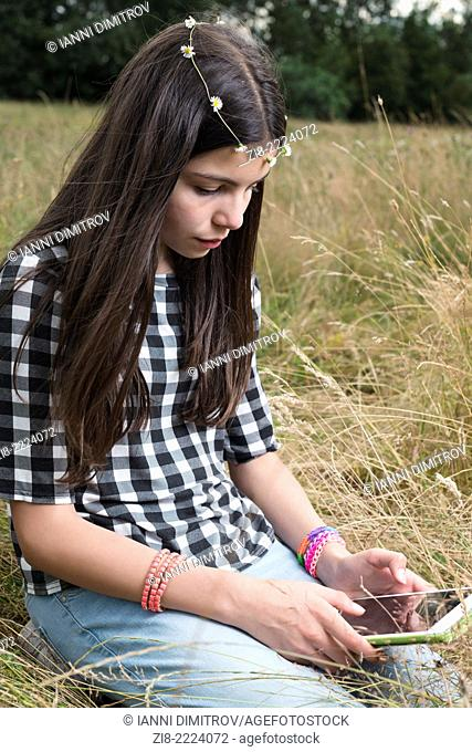 Teenage with a tablet in the park