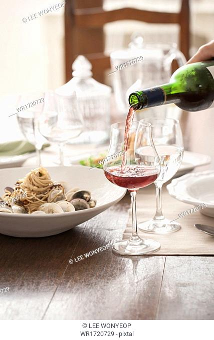A pasta meal next to a wine glass
