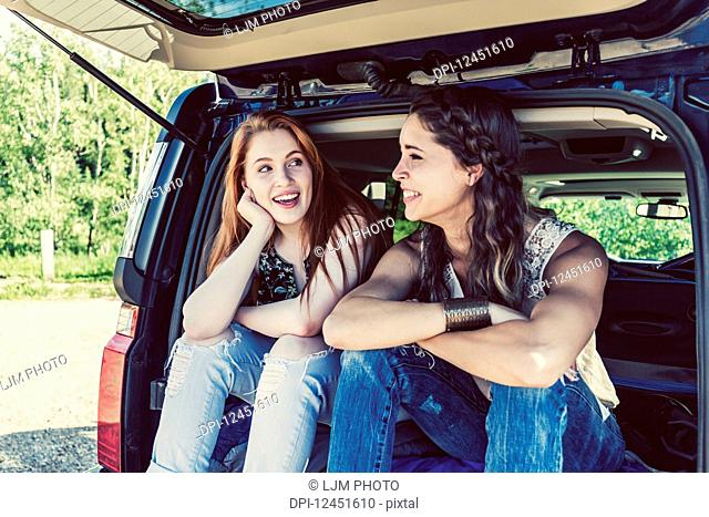 Two young women on a road trip sit in the back of a vehicle talking and laughing together; Edmonton, Alberta, Canada