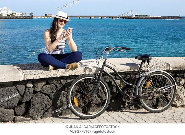 Young smiley woman in hat and sunglasses using device while sitting on quay in Lanzarote, Gran Canaria