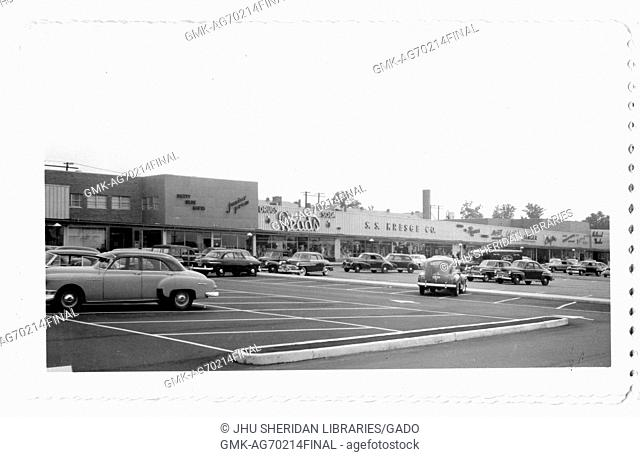 Photograph of the parking lot for the Northwood Shopping Center in Baltimore, Maryland, showing cars and commercial buildings such as Reads, S S Kresge Company