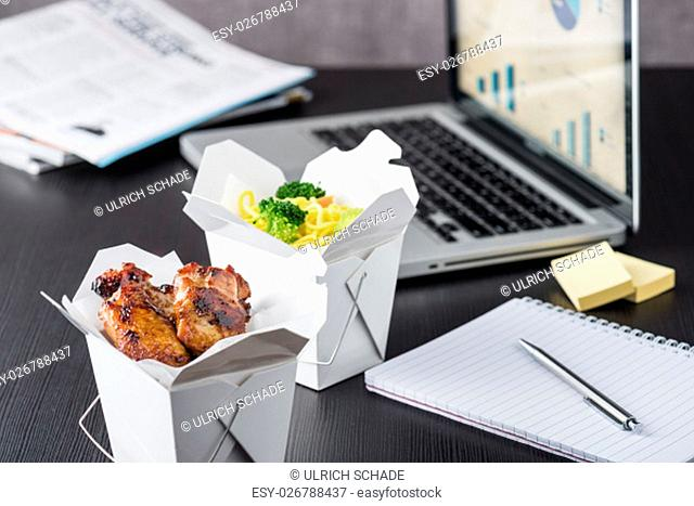 Chicken wings and noodles in noodles box at office lunch