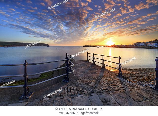 Swanage Bay captured shortly after sunrise in April, with the first rays of sunlight illuminating a stone jetty on the promenade