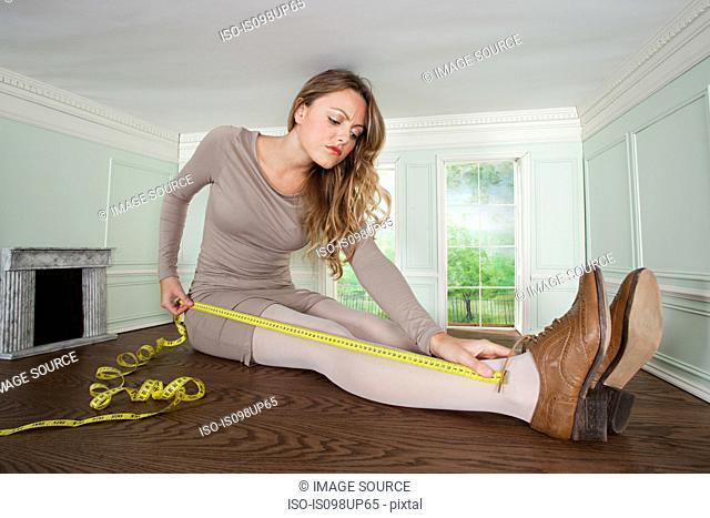 Young woman in small room measuring her leg
