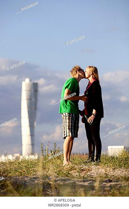 Full length side view of young couple kissing at beach with Turning Torso in background