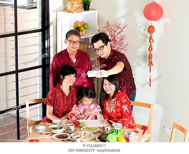 Celebrating Chinese New Year, reunion dinner. Happy Asian Chinese multi generation family with red cheongsam selfie while dining at home